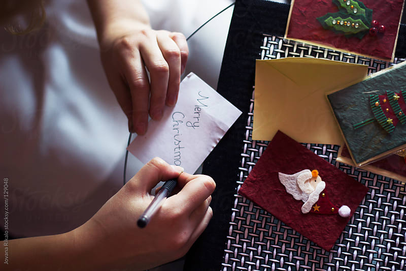 Girl writing on a Christmas card by Jovana Rikalo for Stocksy United