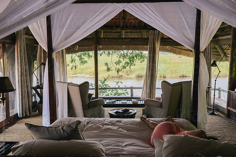 Woman having nap in african safari house with view by Trent Lanz for Stocksy United