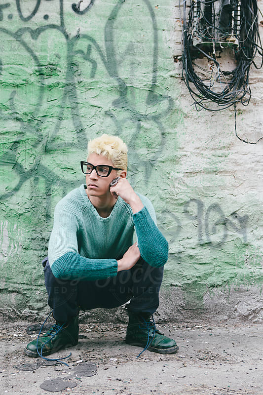 Stylish Young Man with Bleached Blond Hair in Spring and Summer Fashion Squatting against Graffiti Wall by Joselito Briones for Stocksy United