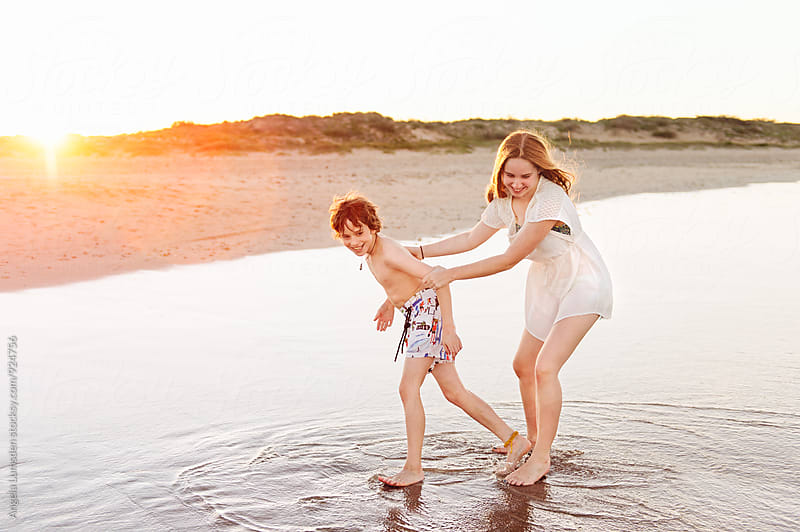 Boy and girl playing at the beach at sunset by Angela Lumsden for Stocksy United
