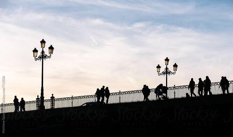 People walking on bridge in Europe by Matthew Spaulding for Stocksy United