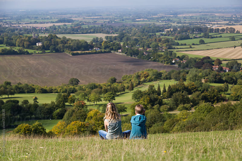 View of English countyside with children sitting on hill by Kirsty Begg for Stocksy United