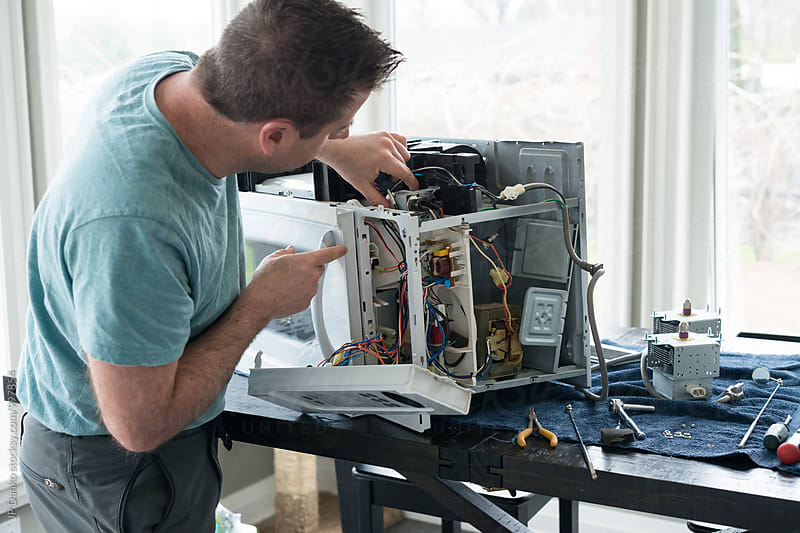 Repair Man Repairing Broken Microwave Oven In Kitchen by JP Danko for Stocksy United