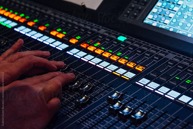 Sound technician's hands on a mixing board by Gabriel (Gabi) Bucataru for Stocksy United