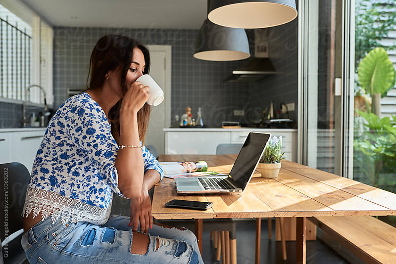 Side view of brunette drinking coffee while working on laptop by Guille Faingold for Stocksy United