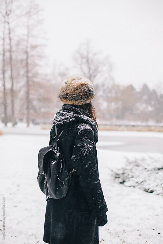 Stylish woman standing in the park during snowy day  by Marija Mandic for Stocksy United