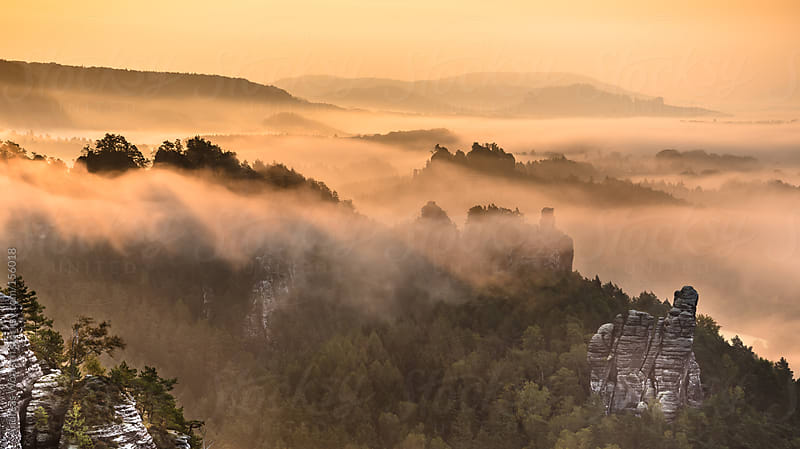 Sunrise over Rocks, Mountains and Fog by Andreas Wonisch for Stocksy United
