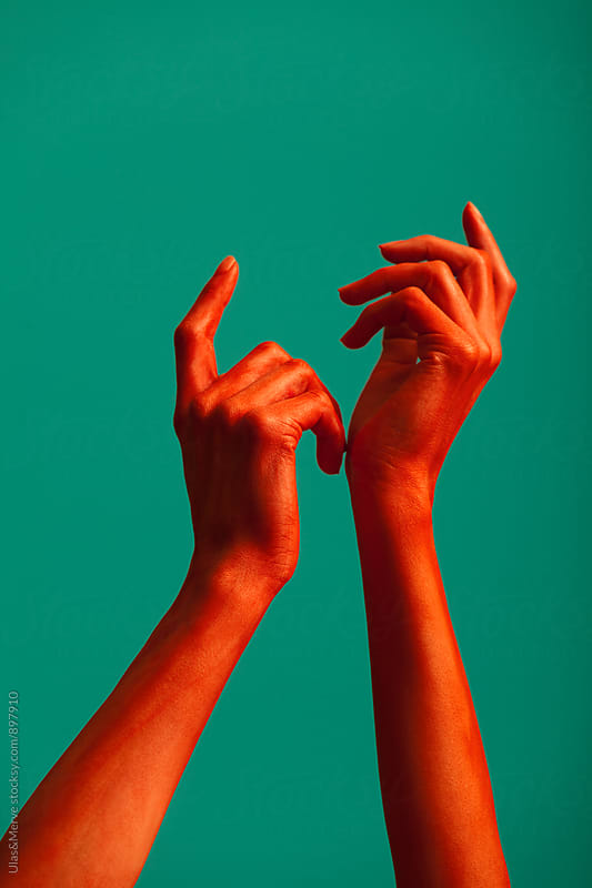 red painted hands of a woman by Ulaş and Merve for Stocksy United