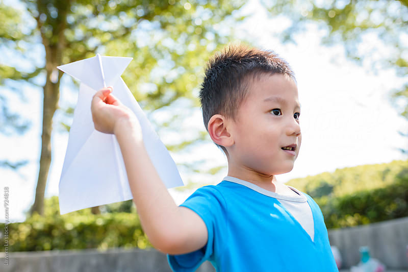 Kid playing paper airplane in sunlight by Lawren Lu for Stocksy United