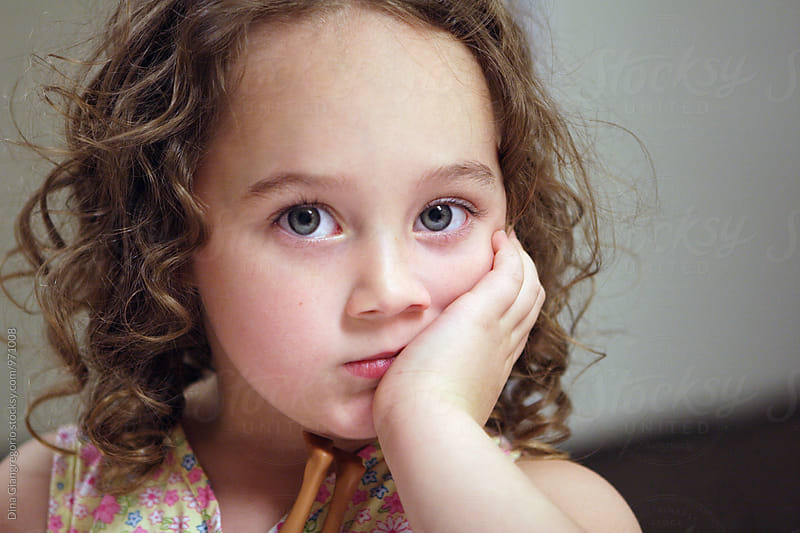 Curly Haired Girl Looking Bored Resting Hand Under Chin by Dina Giangregorio for Stocksy United