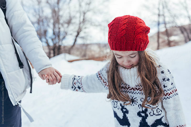 Family taking a walk on snow by Dejan Ristovski for Stocksy United