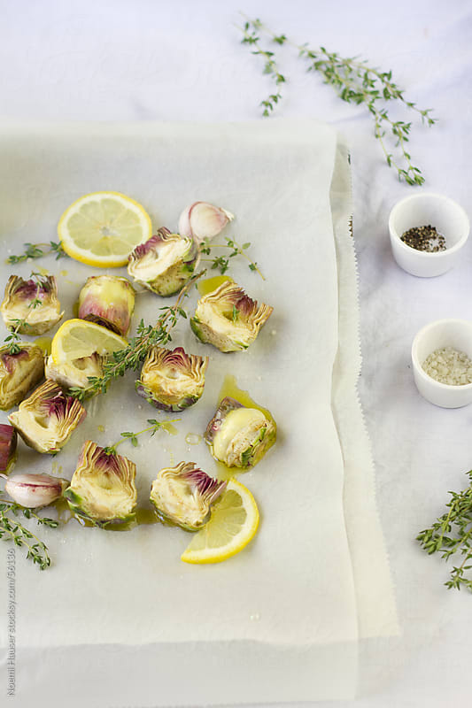 Artichoke hearts on baking paper with thyme by Noemi Hauser for Stocksy United