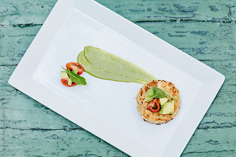 Crab cake starter with avocado and cherry tomatoes by Lior + Lone for Stocksy United