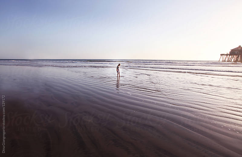 Wide angle view of child on beach near pier by Dina Giangregorio for Stocksy United