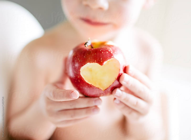Boy holds an apple with a heart shape by Maria Manco for Stocksy United