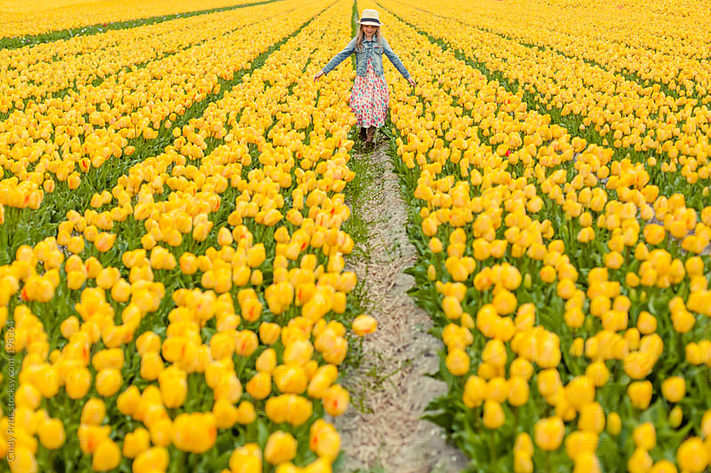 Little girl walking through yellow tulip field with her arms wide by Cindy Prins for Stocksy United