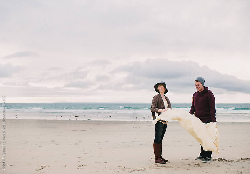 Couple on date at the beach with blanket by Kristin Rogers Photography for Stocksy United