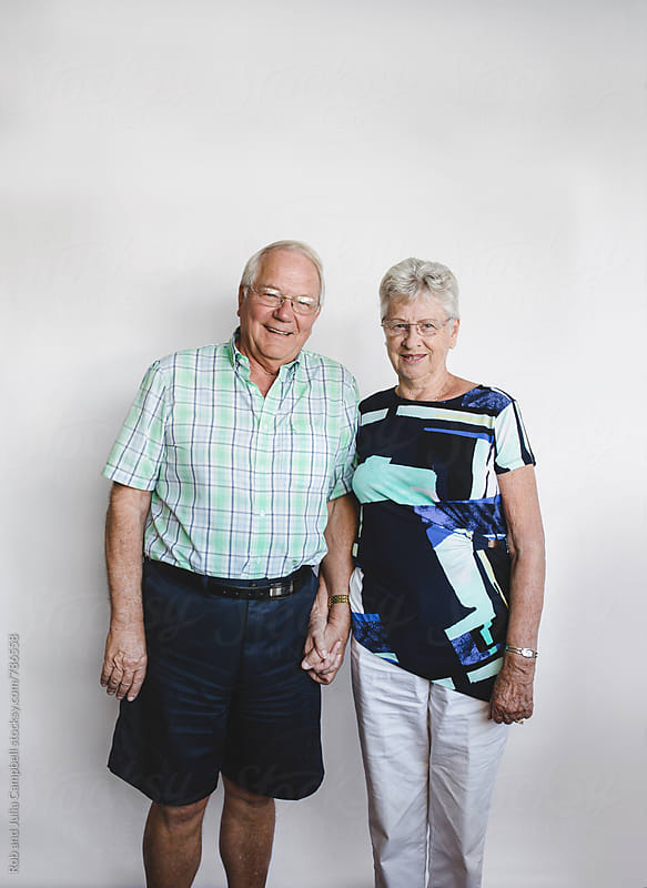 Happy senior couple looking at camera on white background by Rob and Julia Campbell for Stocksy United