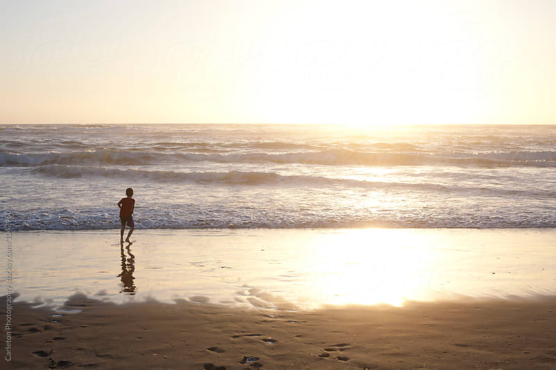 Young boy plays in the ocean during sunset by Carleton Photography for Stocksy United