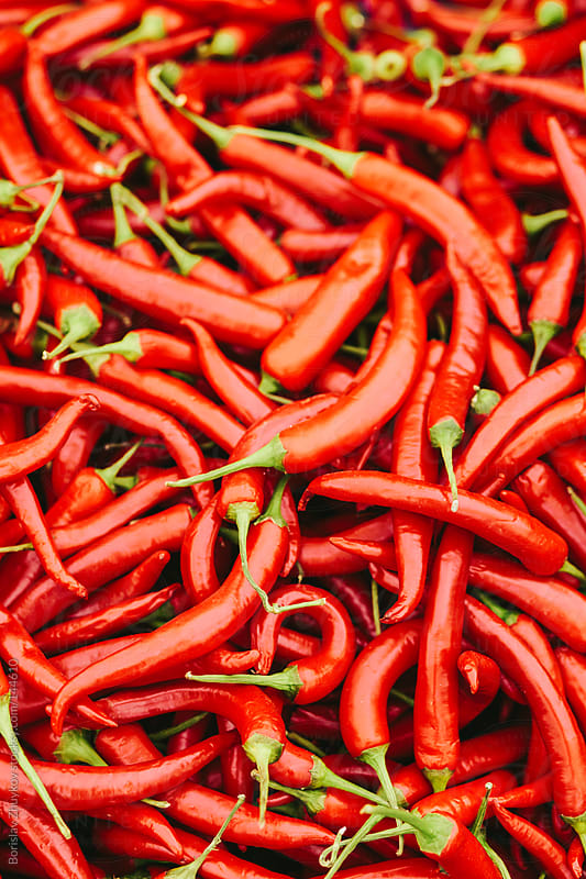 Fresh red hot chily peppers in the market. by Borislav Zhuykov for Stocksy United