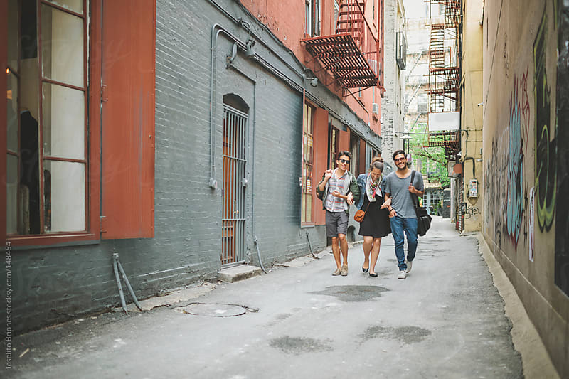 Three Friends Talking and Walking Along a New York City Alley in Lower East Side by Joselito Briones for Stocksy United
