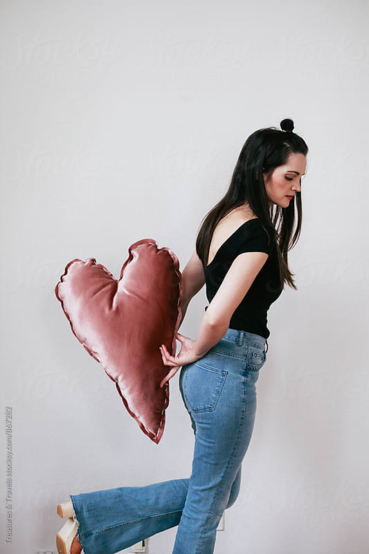 Young woman holding heart pillow by Treasures & Travels for Stocksy United
