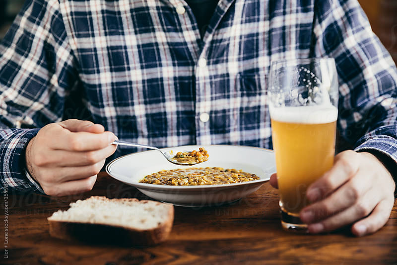Man eating lentil soup and drinking beer by Lior + Lone for Stocksy United