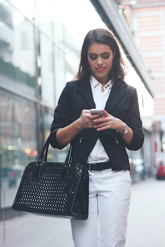 Girl walking down the street and checking her mobile phone by Jovana Rikalo for Stocksy United