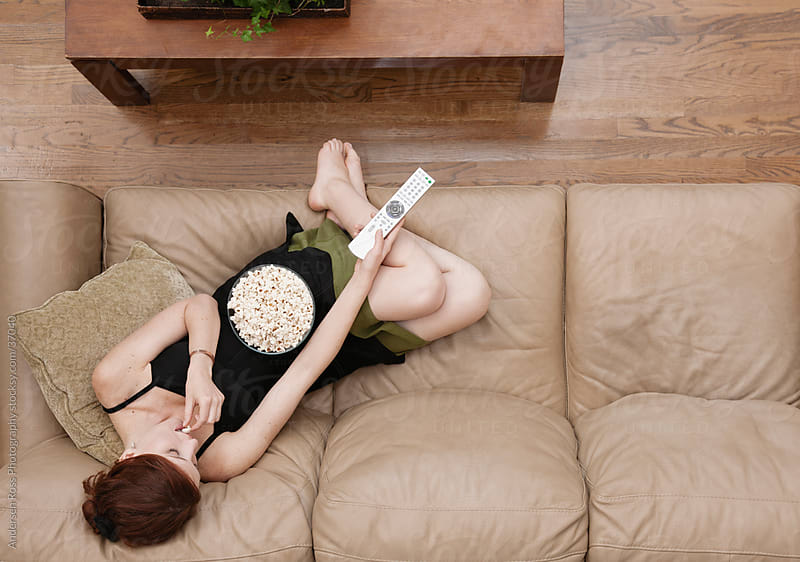 Young woman watching TV and eating popcorn on sofa by Andersen Ross Photography for Stocksy United