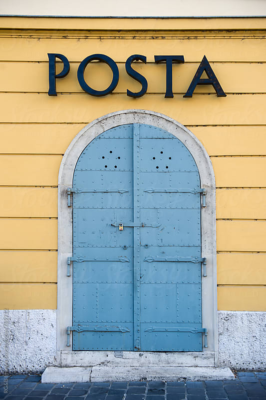 Blue front door of a post office on a yellow wall by RG&B Images for Stocksy United