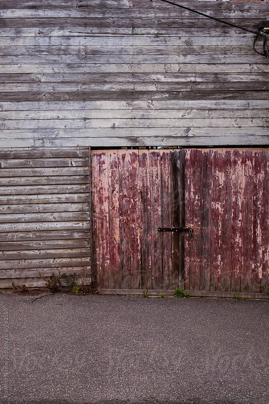 Old rustic barn with red door by Rowena Naylor for Stocksy United