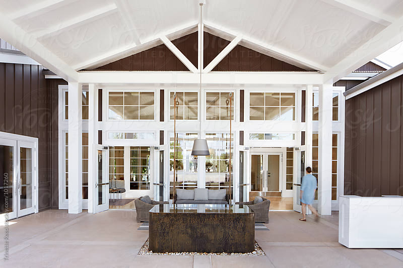 Woman walking into reception area at luxury resort by Trinette Reed for Stocksy United