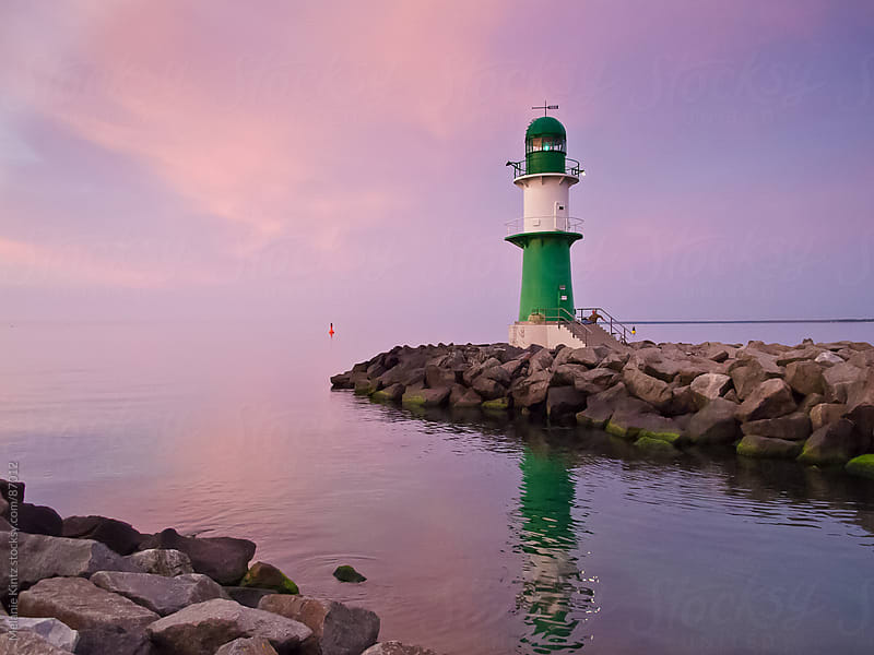 Green Lighthouse at sunset by Melanie Kintz for Stocksy United