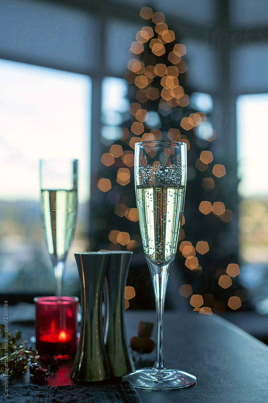 Champagne glasses with a Christmas tree behind them by Carolyn Lagattuta for Stocksy United
