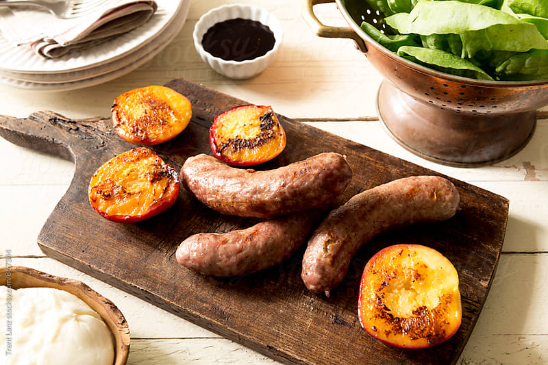 Grilled Italian Chicken sausage with delicious juicy peaches on wooden board by Trent Lanz for Stocksy United