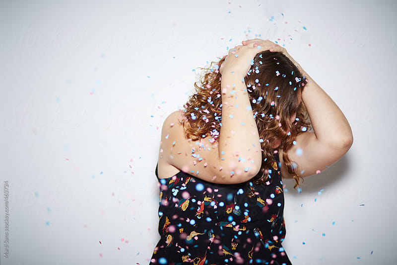 Young woman covering from confetti by Martí Sans for Stocksy United