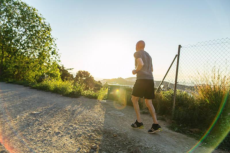Senior man running in the mountain at morning.  by BONNINSTUDIO for Stocksy United