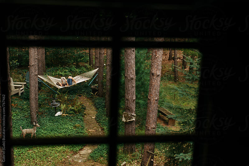 Woman reading in a hammock in a forest by Gabriel (Gabi) Bucataru for Stocksy United