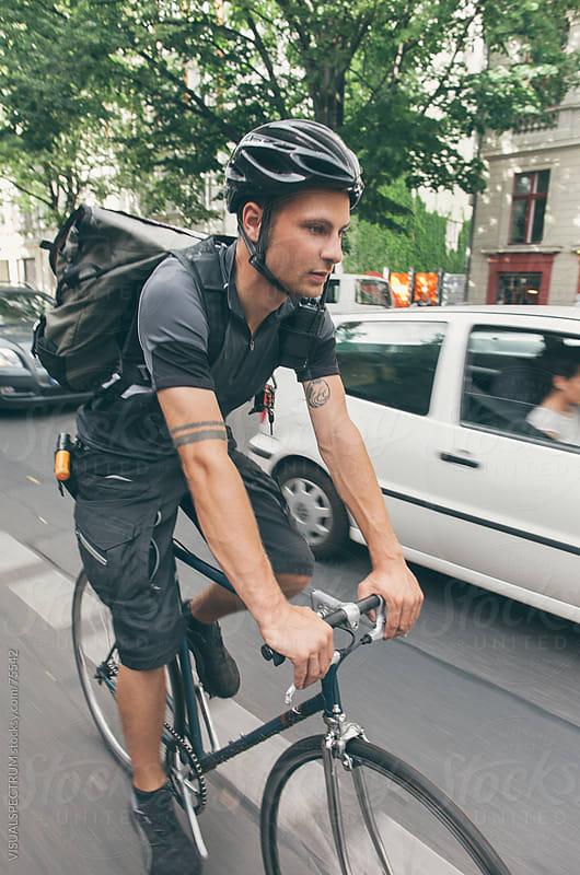 Bicycle Messenger in Car Traffic by VISUALSPECTRUM for Stocksy United