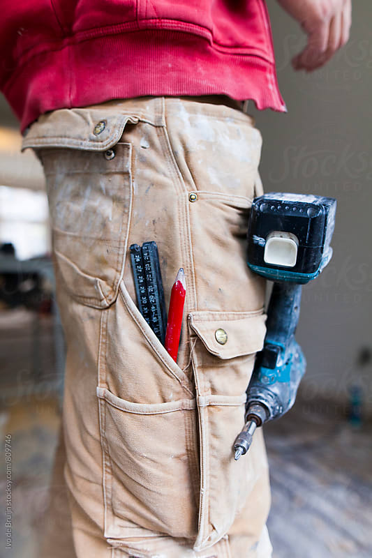 Close up of a pair of working pants with tools in it; a ruler, a pencil and a drill by Ivo de Bruijn for Stocksy United