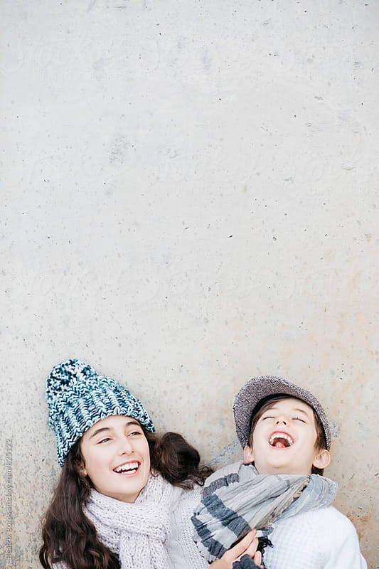 Siblings together laughing in warm wool clothes by Beatrix Boros for Stocksy United