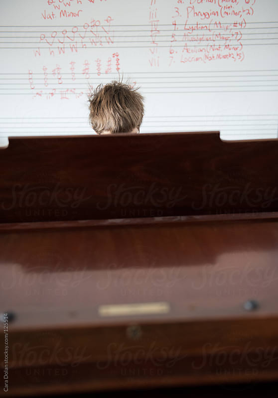 Boy practicing the piano by Cara Dolan for Stocksy United