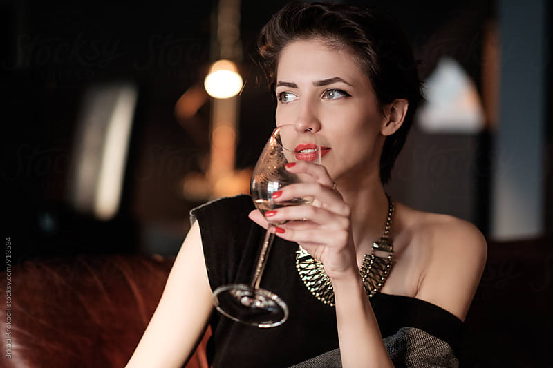Beautiful Brunette Drinking Vine at the Dinner Party by Branislav Jovanović for Stocksy United