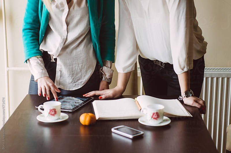 Two businesswomen at workplace by Boris Jovanovic for Stocksy United