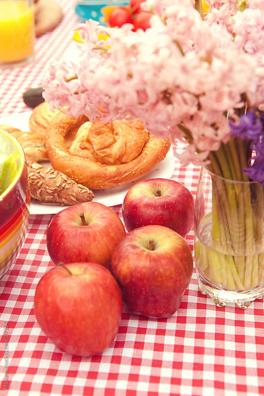 Close up of red apples with colorful breakfast picnic food in the background. by Mosuno for Stocksy United