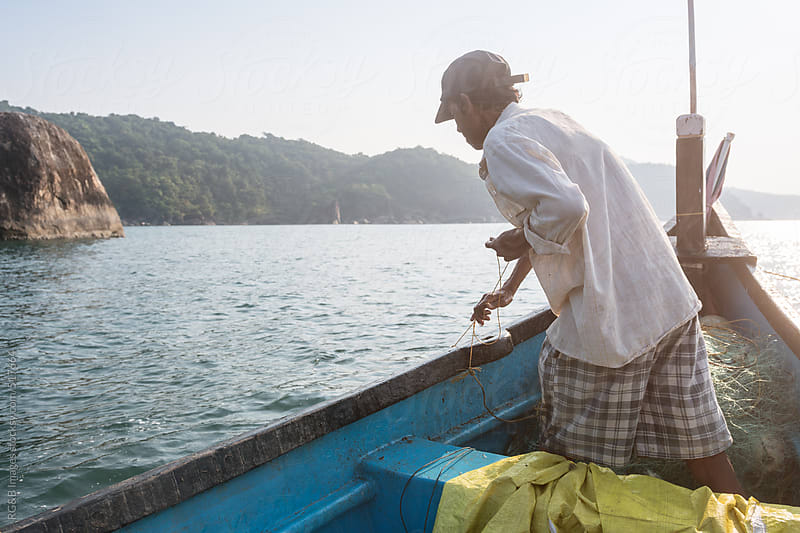 fisherman on boat pulling net from water  by RG&B Images for Stocksy United