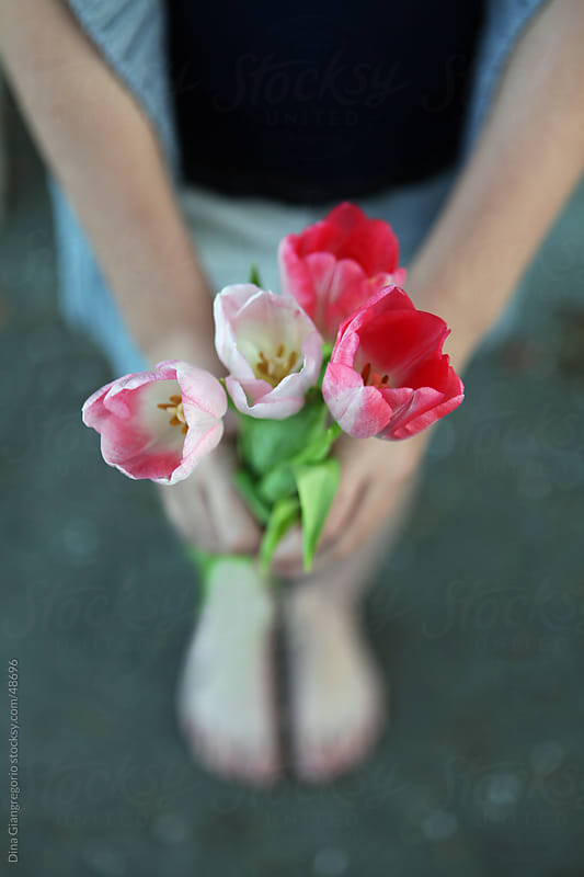 Girl holding pink tulips shown from a downward perspective view by Dina Giangregorio for Stocksy United