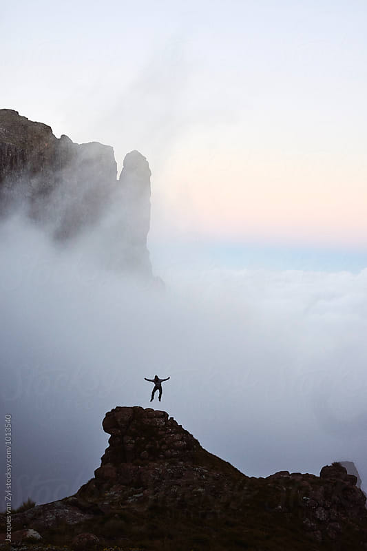 Joyful pumping from a rock peak in majestic misty mountain surroundings.  by Jacques van Zyl for Stocksy United