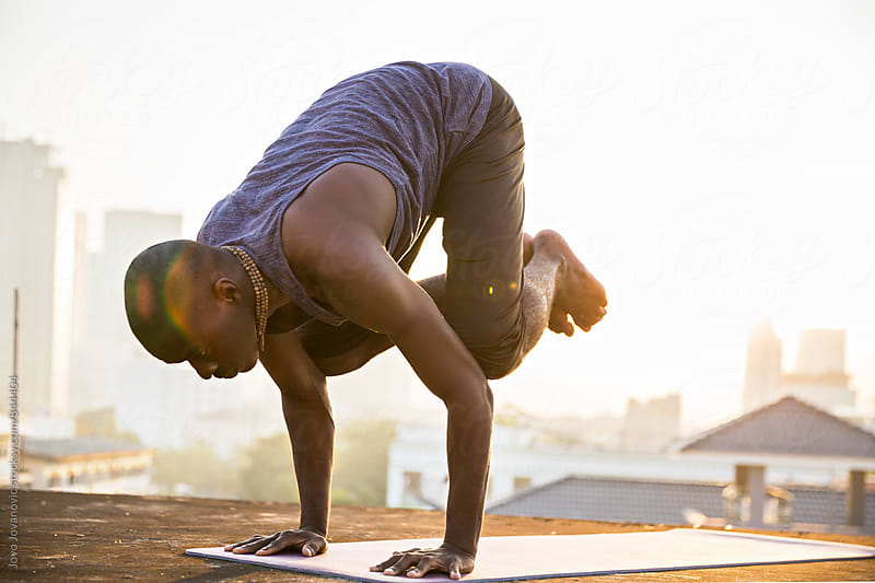 Dark skinned young man doing a bakasana, crane pose during an intense yoga practice  by Jovo Jovanovic for Stocksy United