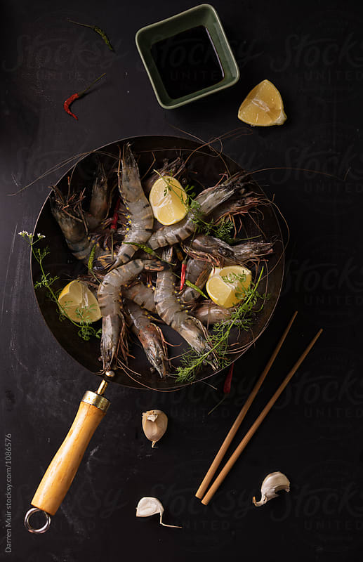 Tiger prawns: Giant tiger prawns in a wok ready to be cooked. by Darren Muir for Stocksy United